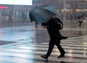 A man struggles with his umbrella in the wind and snow while crossing the street in New York